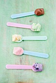 Various types of ice cream on ice cream spoons: vanilla, strawberry, chocolate, blueberry and mint