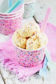 Vanilla ice cream with sugar sprinkles in a pink paper tub