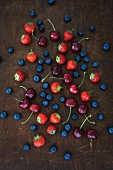 Summer fruits on a wooded board (strawberries, blueberries and cherries)