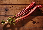 Two bunches of fresh rhubarb stalks on a wooden surface