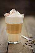 A latte macchiato with green coffee beans