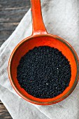 Black cumin in an orange container (seen from above)