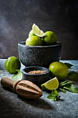 Ingredients for making mojitos: limes, mint and brown sugar