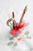 Festive candy canes tied with ribbon arranged in glass
