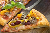 Mexican pizza with minced meat, beans and sweet corn (close-up)