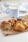 Frühstückssemmel, Croissant und Marmeladengläschen auf Papiertüte