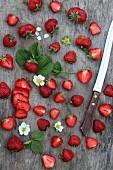 Frische Erdbeeren, ganz und halbiert auf Holzuntergrund