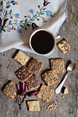 Biscuits with flax seeds, sunflower seeds and sesame seeds served with a cup of coffee