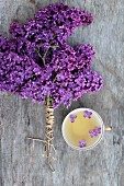 Bund mit violetten Fliederblüten neben Tasse Tee mit Fliederblüten