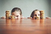 Two little girls looking over the edge of a table at stacks of biscuits