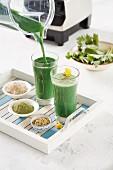 Grünen Smoothie in Glas einschenken