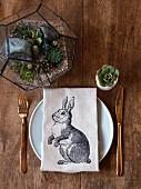 Leinenserviette mit Hasenmotiv auf Gedeck, Mini-Terrarium und Eierbecher mit Sukkulente auf Holztisch