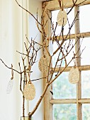Paper Easter eggs hung from branch in front of window