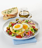 Warm potato salad with peppers, olives, onions and a soft boiled egg