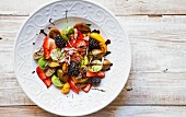 A colourful tomato salad with berries and onions