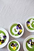Grüne Erbsencremesuppe mit Sauerrahm und Essblüten