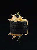 Black food: caviar timbale with fried batter, foam and tarragon on a black reflective surface