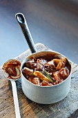 Ox goulash with rhubarb in a saucepan