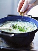 Potato risotto being sprinkled with herbs