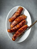 Fat, grilled Sauerländer sausages wrapped in bacon