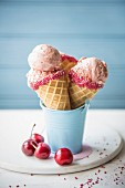 Cherry ice cream in cones with fresh cherries