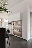 Massgefertigte Küchenschränke zum Teil in Wand eingebaut, beleuchtete Ablagen an grauer Wand, in offener Küche
