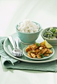 Curry calamari with rice served with cucumber salad and a mint and yoghurt sauce