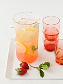 Strawberry lemonade in a glass jug