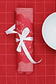 Red linen napkin and lace doily tied with white ribbon on red tablecloth