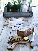 Rye spelt bread with walnuts and cranberries on a wooden board and a wooden table