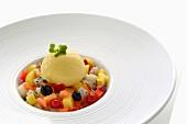 Scoop of vanilla ice cream on a fruit salad