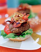A homemade beefburger with bacon and onions