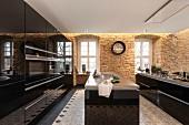 Moderne Küche mit schwarzen Hochglanzoberflächen und freistehenden Theken, Sandsteinwände mit indirekter Beleuchtung und abgehängte Decke