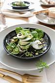 Gedeck mit Spinat-Rettich-Salat und Misodressing auf schwarzem Teller