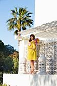 Brünette Frau in gelbem A-Linien-Kleid, rosa-gelbem Cardigan und Pumps