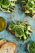 Slices of grilled bread topped with avocado, green asparagus and cress