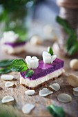 A slice of cheese cake with white chocolate, Macadamia nuts and blueberry cream