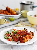 Chicken kebabs with a cucumber and tomato salad