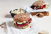 Vegan wholemeal burgers with shredded cabbage, carrots, lettuce and beetroot fritters