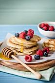 Ein Stapel Pancakes mit Beeren und Honig