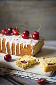 Cherry cake with icing, fresh cherries and flaked almonds, sliced