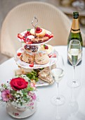English afternoon tea with sandwiches, scones, petit fours and champagne