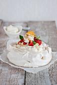 Baisertorte Pavlova mit Schlagsahne, Obst und Mandeln