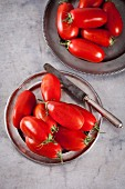 San Marzano tomatoes on a metal plate with a knife (seen from above)
