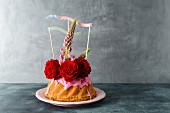 A mini Bundt cake decorated with icing, roses, Lupin flowers and paper flags