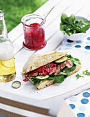 Ciabatta sandwich with steak strips, vegetables and beetroot tzatziki