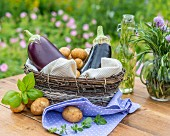 Aubergines, potatoes and herbs in a basket on a garden table