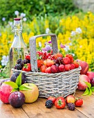 Berries and fruits in a basket and next to it on a garden table