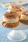 Profiteroles filled with cream on a cake stand
