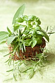 Rosemary, sage and basil in a wicker basket